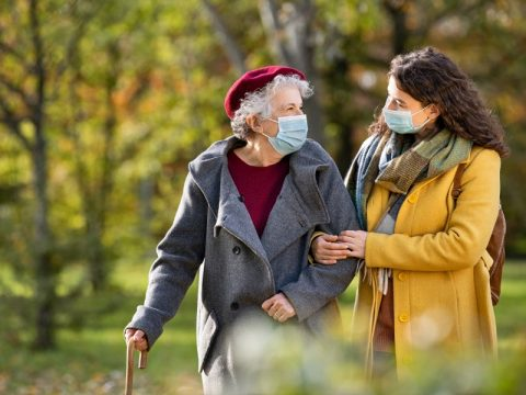 A granddaughter is assisting her grandmother on a walk in the park. They are both wearing masks.