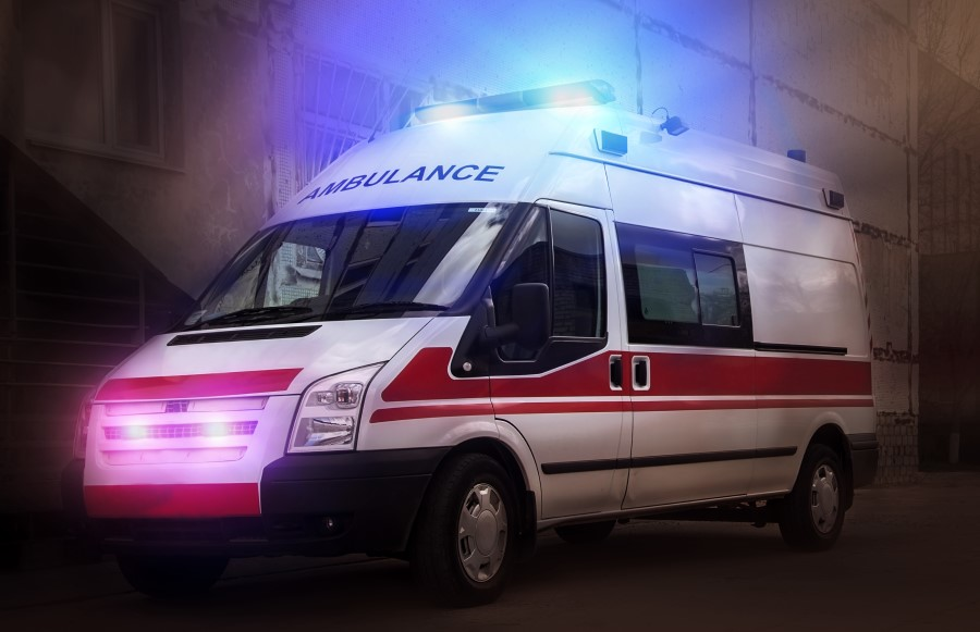 An image of an ambulance, lights are on, parked in front of a hospital